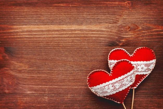 Twee vilten harten met veters, symbool van liefde op hout