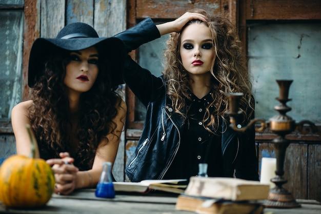 Twee vintage heksen zitten aan de tafel op een verlaten plek aan de vooravond van halloween