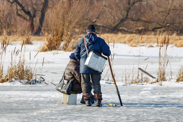 Twee vissers op het ijs van het meer. ijs wintervissen
