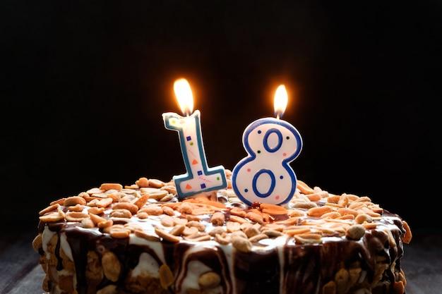 Twee vlammende kaarsen op verjaardagstaart op zwarte achtergrond