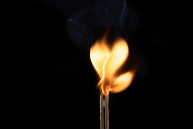 Twee vlammende lucifers met rook en vuur in de vorm van een hart
