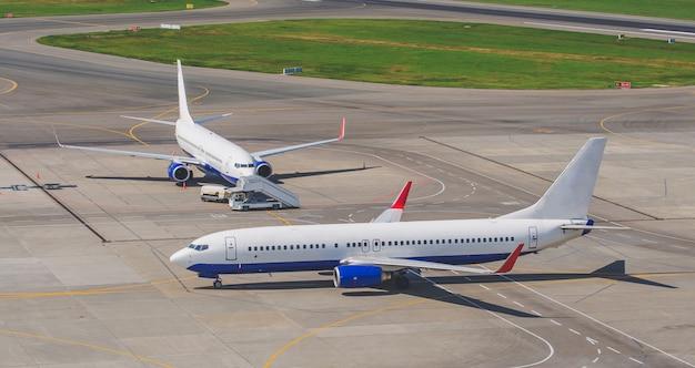 Twee vliegtuigen taxiën op de luchthaven, op het stuur en de loopplank.