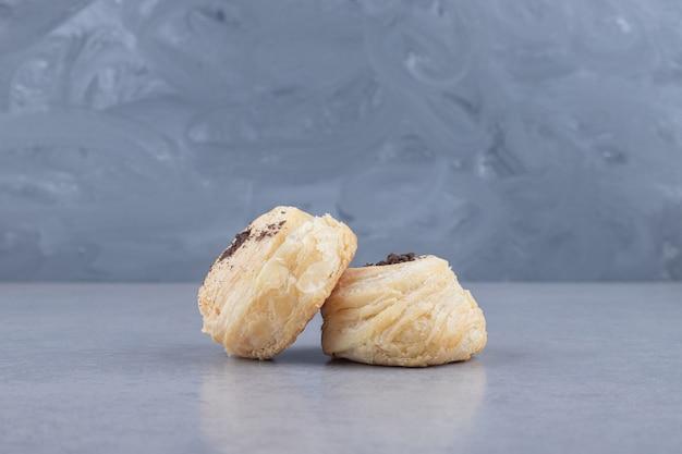 Twee vlokkige koekjes weergegeven op marmer