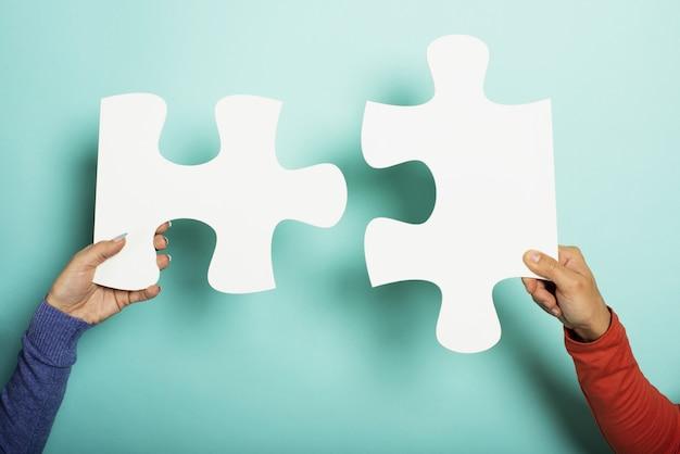 Twee volkeren voegen zich bij een puzzel op cyan. bovenaanzicht