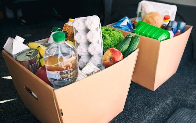Twee volle kartonnen eco dozen met producten uit de kruidenierswinkel in de auto