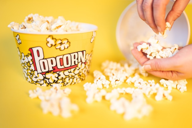 Twee volle popcornemmers waarvan één omgegooid en twee handen die popcorn pakken en eten
