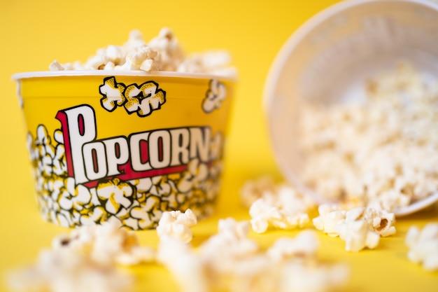 Twee volle popcornemmers waarvan één omgevallen en omringd door veel popcorn op een gele achtergrond yellow