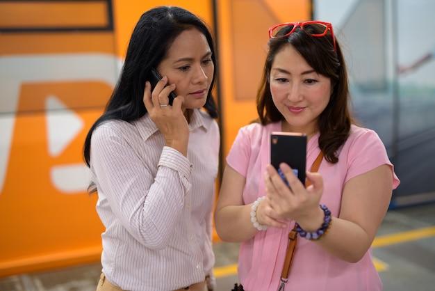 Twee volwassen aziatische vrouwen samen op het skytrain-station in bangk