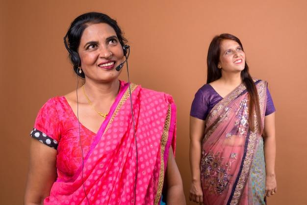 Twee volwassen indiase vrouwen die sari indiase traditionele kleding dragen, samen met een hoofdtelefoon