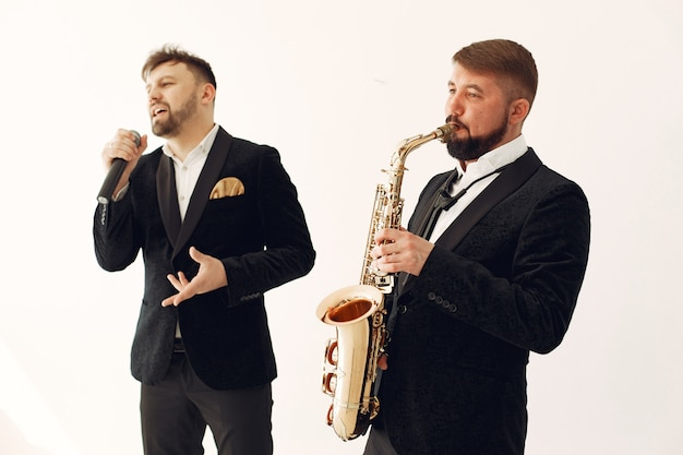 Twee volwassen muzikanten staan in de studio