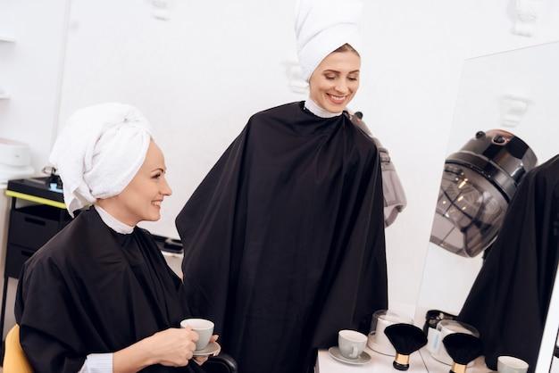 Twee volwassen vrouwen die met handdoeken op hun hoofden koffie drinken.