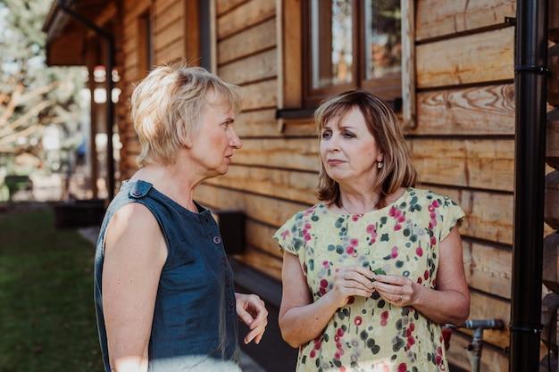 Twee volwassen vrouwen van 55 jaar oud praten schattig op de achtergrond van een houten huis