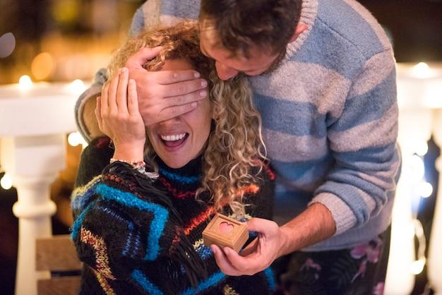 Twee volwassenen samen in restaurant of thuis - romantische man die een cadeautje geeft in een kleine doos met een ring erin - paar getrouwde mensen