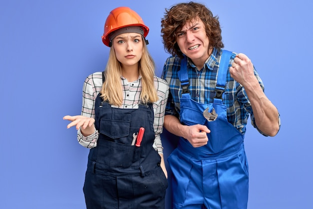 Twee voormannen die ontevreden zijn over de kwaliteit van het reparatiewerk van de bouwer, staan serieus naar de camera te kijken