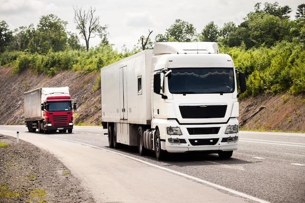 Twee vrachtwagens die in de zomer over een weg rijden