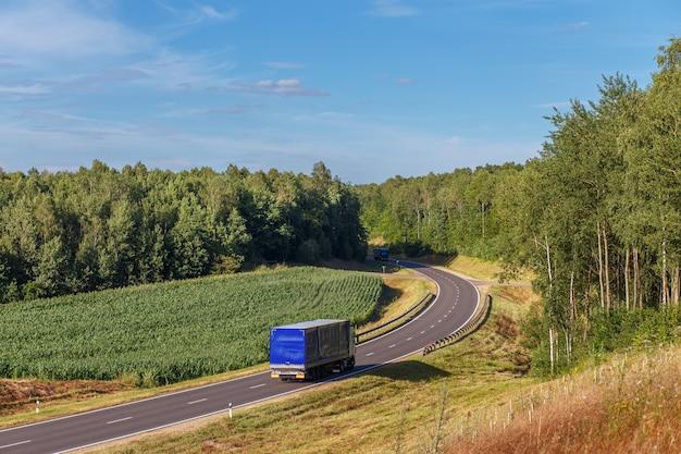 Twee vrachtwagens rijden naar elkaar toe langs een bocht in de weg in een landelijk gebied