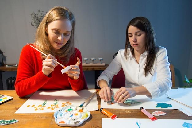 Twee vreedzame meisjes die van het eenvoudige schilderen genieten