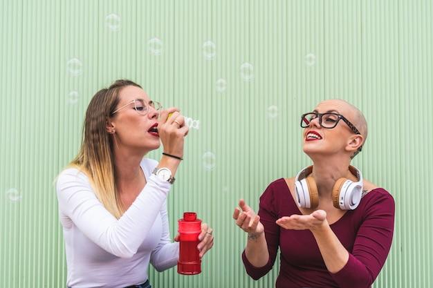 Twee vriend meisjes spelen met zeepbel buitenshuis.