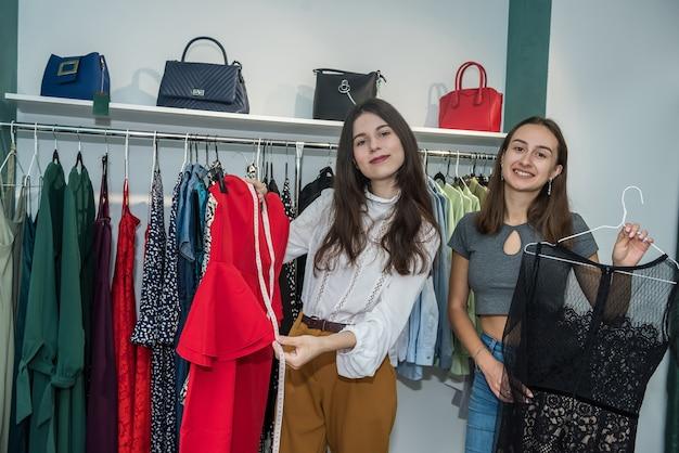 Twee vriendelijke meisjes tijd doorbrengen om te winkelen in de modewinkel. levensstijl
