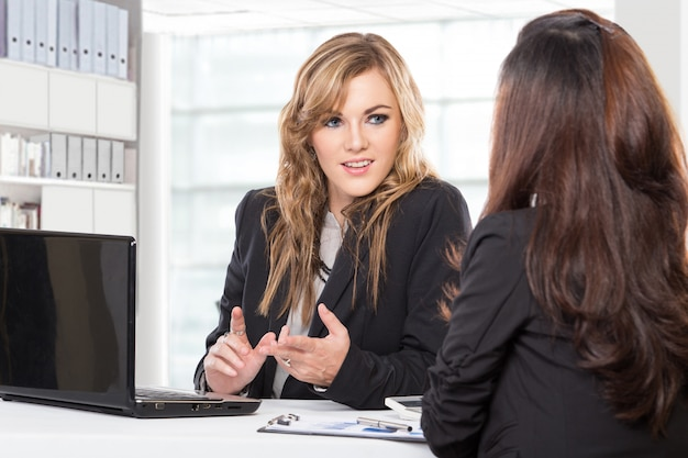 Twee vriendelijke zakenvrouwen zitten en bespreken van nieuwe ideeën met behulp van laptopcomputer
