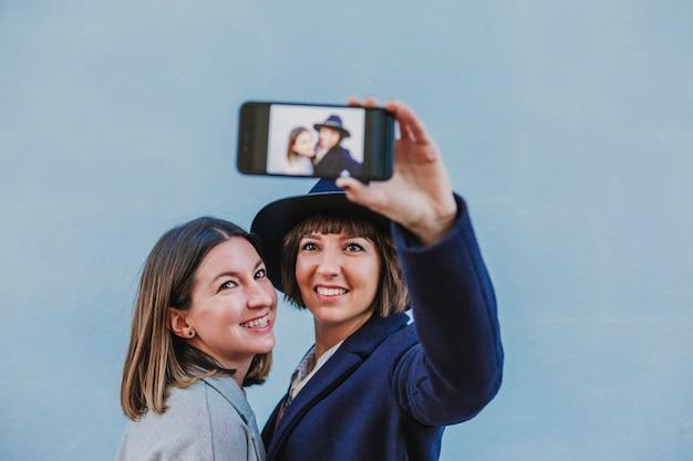 Twee vrienden buitenshuis met stijlvolle kleding die een selfie met mobiele telefoon
