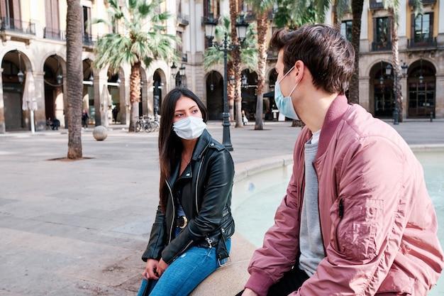 Twee vrienden die een gezichtsmasker dragen en buiten praten.