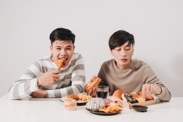 Twee vrienden die hamburgers eten. frietjes, plezier maken en lachen