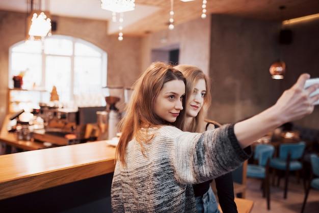 Twee vrienden die koffie drinken in een café, selfies nemen met een smartphone en plezier maken met het maken van grappige gezichten. focus op het meisje aan de linkerkant