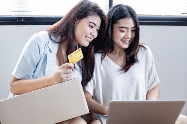 Twee vrienden die online met creditcard en laptop thuis winkelen.