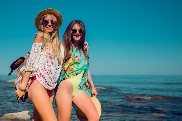 Twee vrienden die op het strand wandelen en plezier hebben.