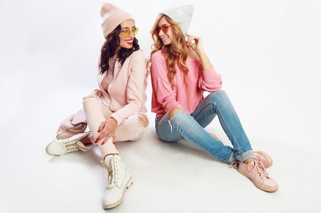 Twee vrienden die op witte vloer in studio koelen. schattige roze outfit. stijlvolle schoenen.