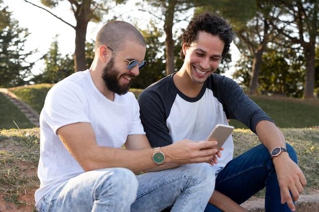 Twee vrienden die plezier hebben met mobiel in het park bij zonsondergang