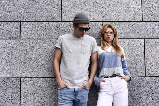 Twee vrienden die tegen een muur leunen en elkaar negeren. technologie verslaving concept, man en een vrouw op grijze muur achtergrond.