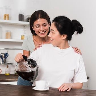 Twee vrienden die thuis samen koffie hebben