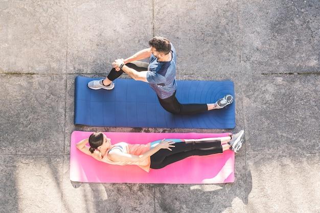 Twee vrienden die zich buiten op yogamatten uitrekken