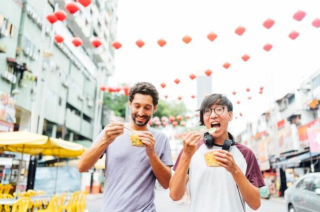Twee vrienden eten van chinees eten op straat