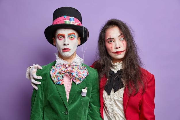 Twee vrienden gekleed in halloween carnavalskostuums omhelzen elkaar en hebben vriendschappelijke relaties, dragen griezelige make-up en vieren feestdagen geïsoleerd op een paarse muur