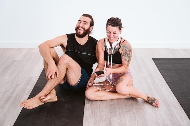 Twee vrienden in de sportschool luisteren naar muziek op mobiele telefoon en headset en plezier maken