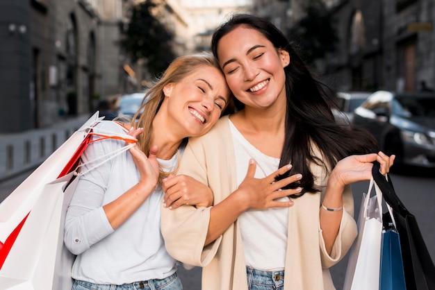 Twee vrienden in de stad die genieten van een dagje winkelen