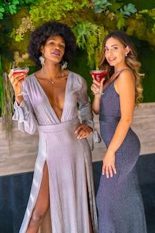 Twee vrienden in galajurken met een cocktail op een feestje in een hotel, lifestyle. glamour lifestyle, exclusief feest