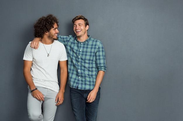 Twee vrienden in vrijetijdskleding staan en lachen samen
