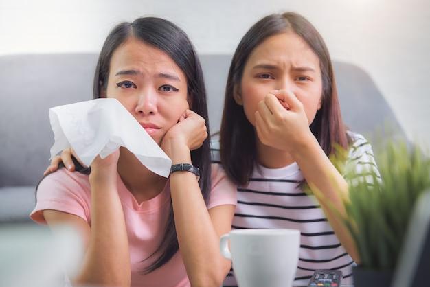 Twee vrienden kijken naar een serie film op tv en emotioneel huilen in vakantietijden in de woonkamer thuis.