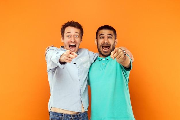 Twee vrienden knuffelen elkaar wijzende vinger en kijken naar de camera en schreeuwen of schreeuwen