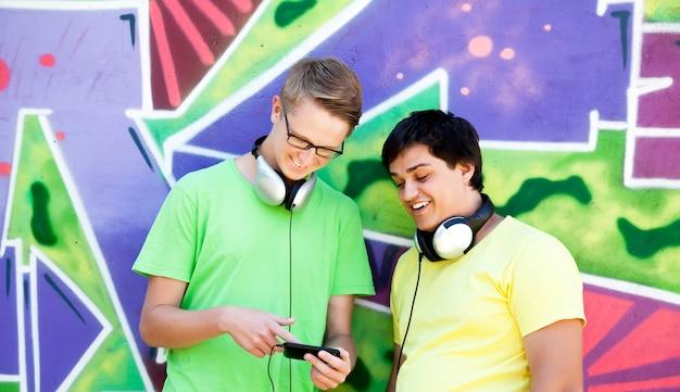 Twee vrienden luisteren muziek in de buurt van graffitimuur.