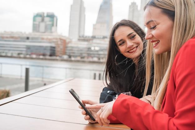 Twee vrienden met behulp van hun mobiele telefoon zittend in de coffeeshop.