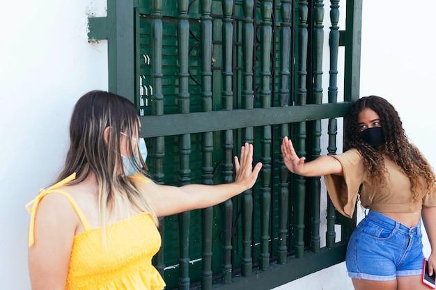 Twee vrienden met beschermende maskers begroeten elkaar buitenshuis