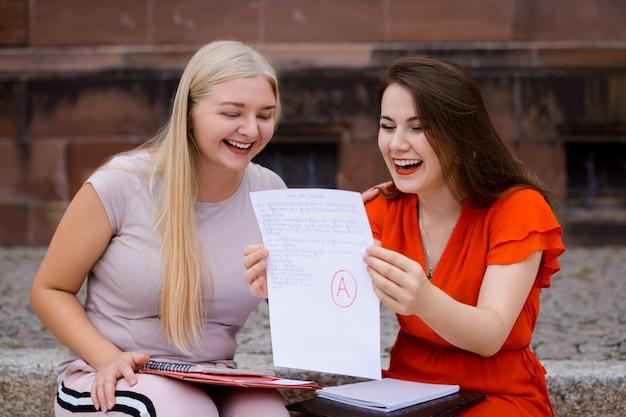 Twee vrienden met examenresultaten ontvangen graag het hoogste a-cijfer