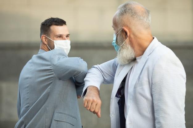 Twee vrienden met gezichtsmasker begroeten elkaar met de elleboog op straat