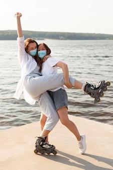 Twee vrienden met gezichtsmaskers en rolschaatsen die plezier hebben bij het meer