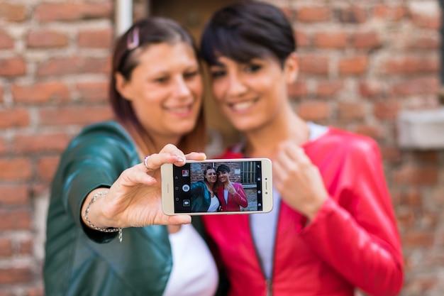Twee vrienden nemen een selfie in een stedelijke straat